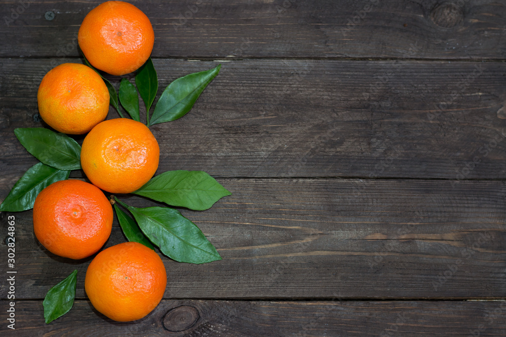 Fototapety, obrazy: Fresh orange mandarins with green leaves on a dark wooden table. The concept of a healthy diet and vegetarianism. Top view.
