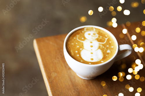 Tasty cappuccino with Christmas snowman art with some blurred lights.