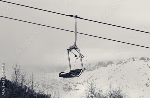 Photo  Chair lift and snowy mountains in haze