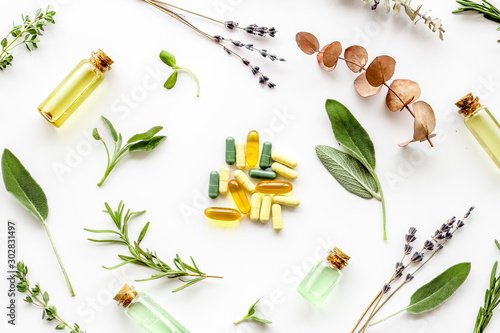 Medicine made from wildflowers and herbs with essential oils on white background Canvas Print