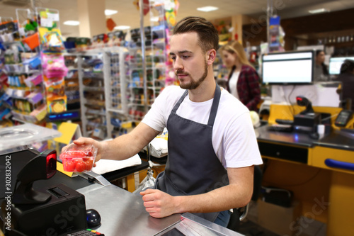 Cuadros en Lienzo Male cashier checking out goods in supermarket