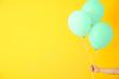 Leinwandbild Motiv Female hand with air balloons on color background