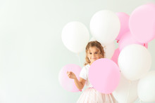 Little Girl With Balloons On Light Background