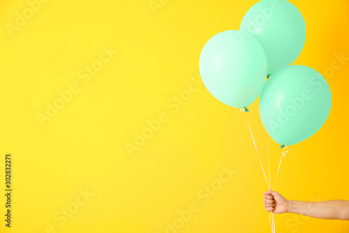 Photo  Female hand with air balloons on color background