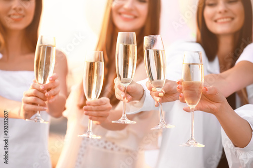 Foto auf Leinwand Alkohol Beautiful young women drinking champagne at hen party outdoors
