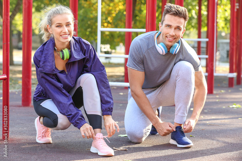 Pinturas sobre lienzo  Sporty young couple tying shoelaces on athletic field outdoors