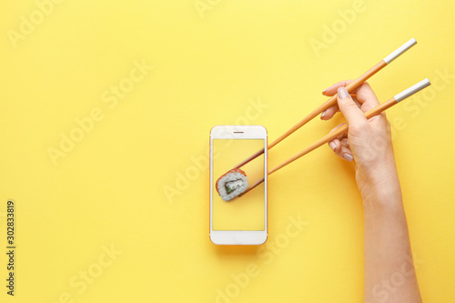 Fototapeta Female hand holding chopsticks and mobile phone with tasty sushi roll on screen against color background obraz