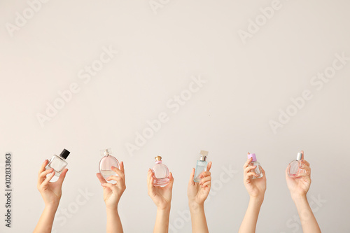 Obraz Female hands with different perfume bottles on grey background - fototapety do salonu