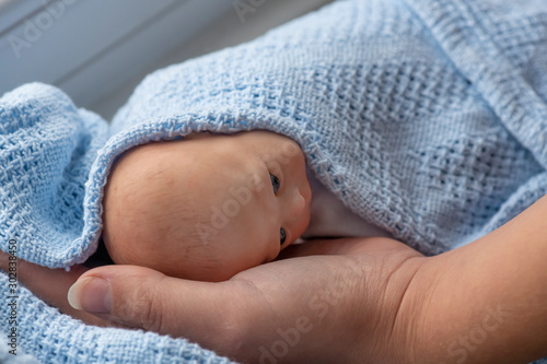 Fotografía  premature newborn baby wrapped in blue blanket with mothers  arm and hand repres