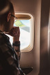 A man looks thoughtfully out the window of an airplane - an important decision to change his life