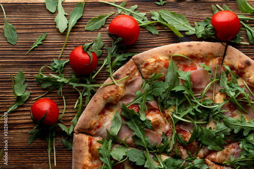 Close up of parma ham pizza with fresh arugula and cherry tomatoes on wooden tab Wallpaper Mural