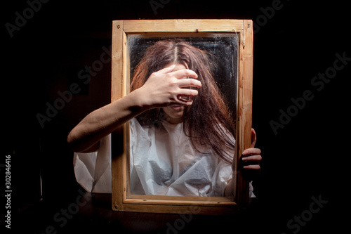 A mystical and frightening portrait of a girl looking through a frame Wallpaper Mural
