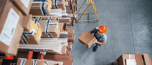 Top View Of Male Worker In Warehouse With Box In Hands