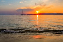 Single Sailing Ship On The Sea With The Beautiful Sunset In The Background In Skiathos, Greece