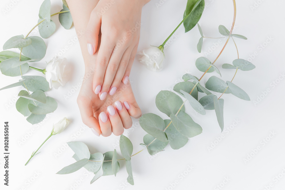 Fototapeta Stylish plain female hand manicure gel polish on white flower background eucalyptus, top view. Concept natural organic skin care