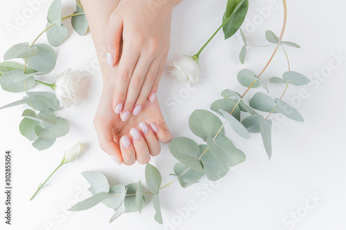 Fotobehang Spa Stylish plain female hand manicure gel polish on white flower background eucalyptus, top view. Concept natural organic skin care