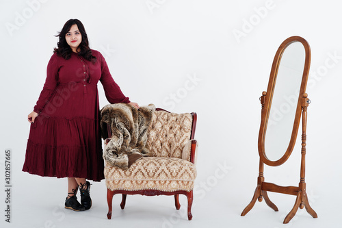 Fotomural  Attractive south asian woman in deep red gown dress posed at studio on white background against mirror and chair