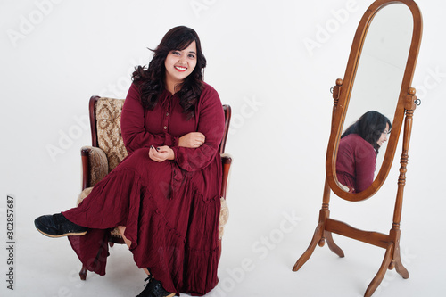 Fotomural  Attractive south asian woman in deep red gown dress posed at studio on white background against mirror and sitting at chair