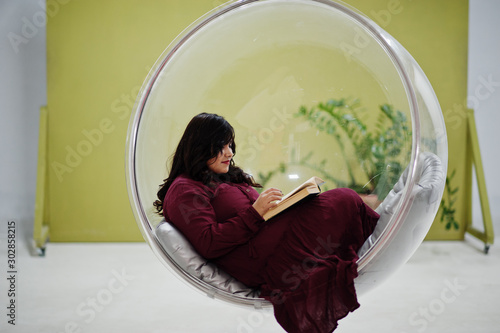 Cuadros en Lienzo Attractive south asian woman in deep red gown dress posed at studio and read a book at rocking chair ball