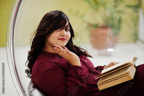 Fotografía Attractive south asian woman in deep red gown dress posed at studio and read a book at rocking chair ball