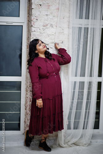 Fotomural Attractive south asian woman in deep red gown dress posed at studio against windows in night