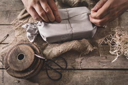 man is wrapping a gift with natural materials and organic cotton, ecological and Wallpaper Mural