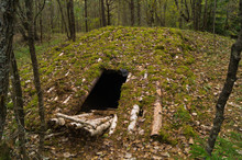 Military Underground Bunker Camouflaged By Logs And Moss Among The Autumn Forest