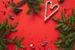 canvas print picture - Christmas / New Year composition. Mockup frame with copy space, fir branches, sweets, decorations on deep red background. Flat lay, top view colorful festive holiday concept.