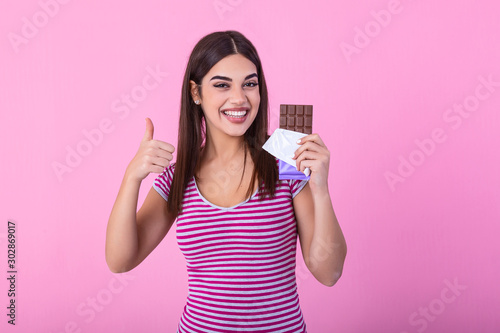 Portrait of a happy young woman with chocolate bar isolated over pink background showing thumbs up Wallpaper Mural