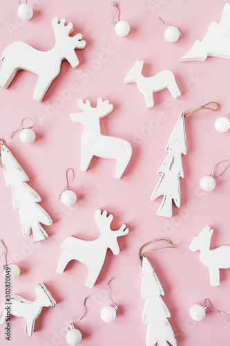 Christmas / New Year holiday composition. Christmas baubles, toy deers, fir-tree on pink background. Flat lay, top view festive pattern. - 302870049