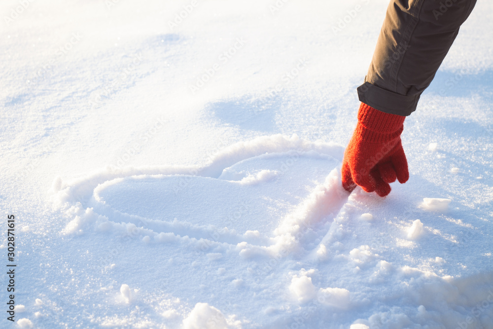 Fototapeta Female Hand in Red Glove Draws Heart on the Snow. Winter Concept