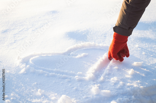 Cuadros en Lienzo  Female Hand in Red Glove Draws Heart on the Snow. Winter Concept