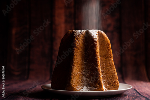 pouring icing sugar on italian pandoro christmas cake with warm natural light up Canvas Print