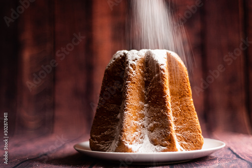 Photo icing sugar pouring on italian pandoro christmas cake with warm natural light up