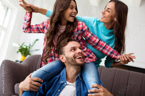 Obraz Playful spirit. Young gorgeous woman is playing with her cute little daughter and husband in their cozy apartment, having fun and laughing together. - fototapety do salonu