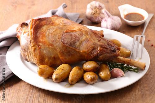 Photo roasted lamb leg with potato and sauce on wood background