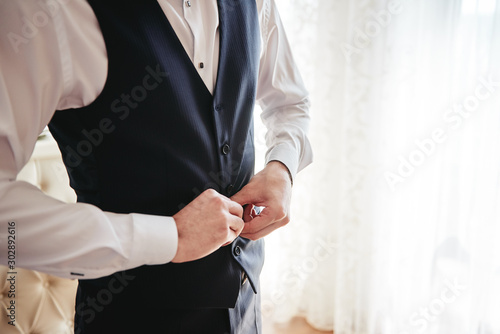 Man in white shirt buttoning waistcoat in room indoors, close up Fototapeta