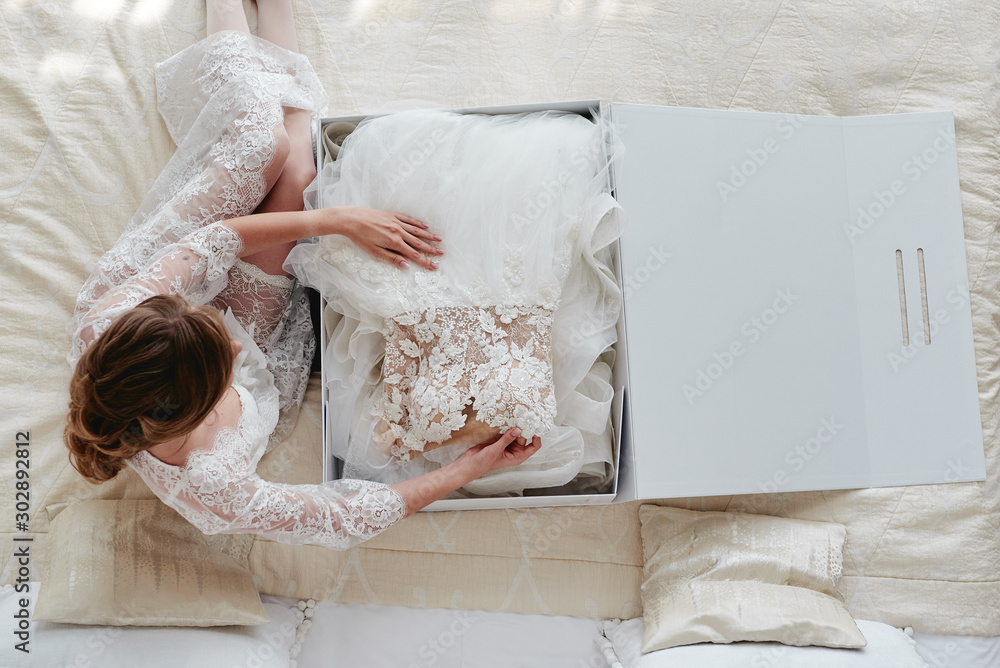 Fototapeta Portrait of beautiful bride in dressing gown holding luxury wedding dress on bed, copy space. Wedding concept. Top view, above