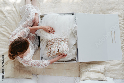 Pinturas sobre lienzo  Portrait of beautiful bride in dressing gown holding luxury wedding dress on bed, copy space
