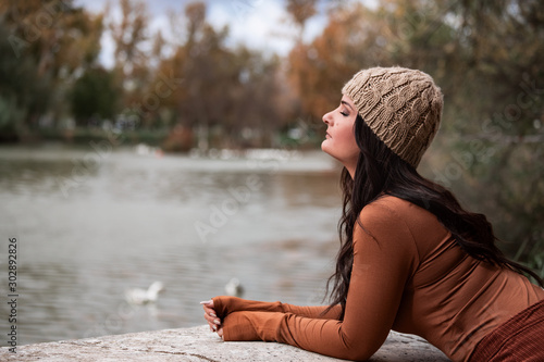 sad woman looking towards a lake Wallpaper Mural