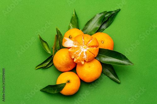 Fototapeta Mandarynki  dojrzale-mandarynki-z-liscmi-swieze-owoce-na-bialym-tle-na-zielonym-tle