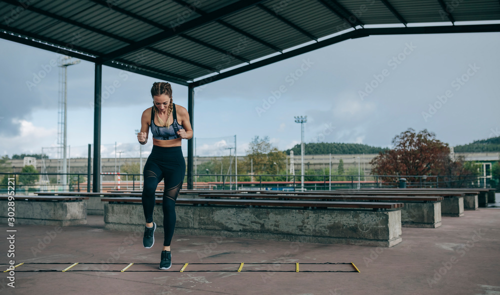 Fototapeta Young sportswoman training jumping on an agility ladder outdoors