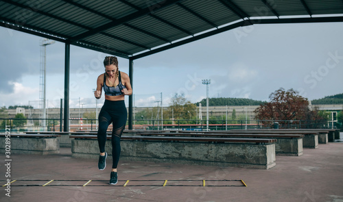 Photo Young sportswoman training jumping on an agility ladder outdoors