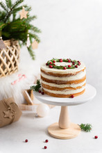 Christmas Composition. Festive Cake Decorated With Rosemary And Cranberries, Gifts And Fir Tree On White Background. Christmas, Winter, New Year, Bakery, Confectionery Concept. Side View, Copy Space