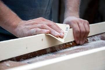 carpenter polishes wood with sandpaper