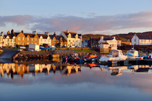 A View Of The Rocky Shore Of A Small Town Port Ellen At Sunrise. Morning Sunlight. Country Houses, Fishing Boats And Yachts Close-up. Isle Of Islay, Inner Hebrides, Scotland, UK