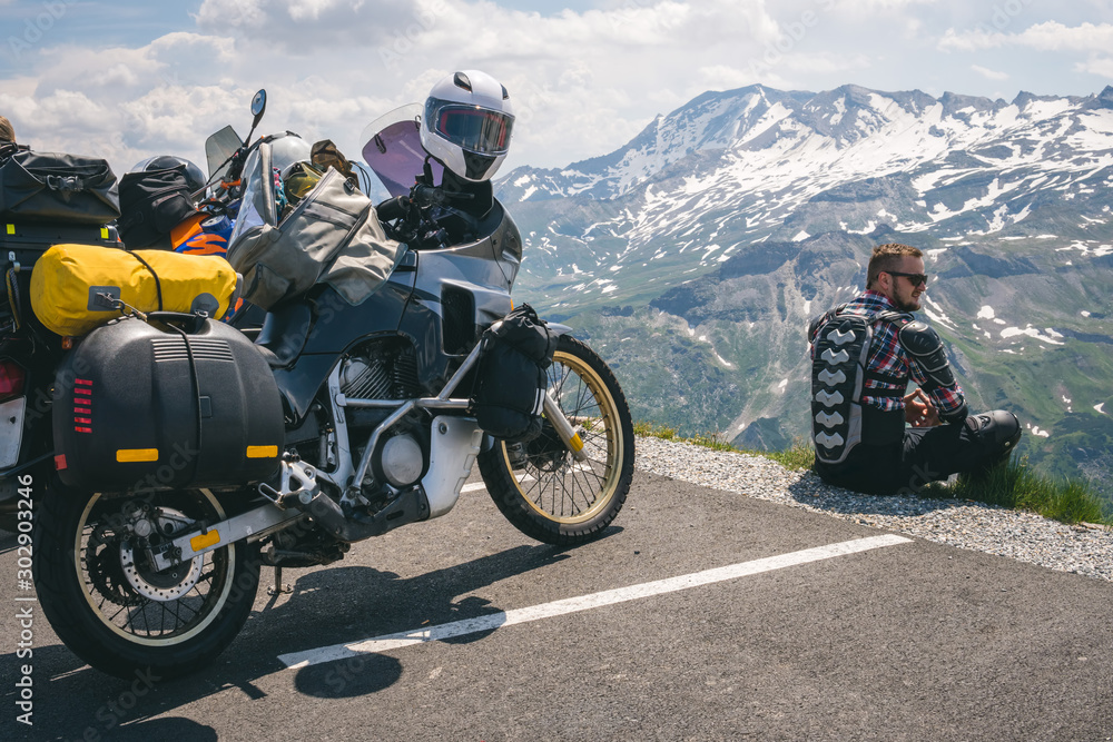 Fototapeta A motorcycle traveler sitting on the edge of the earth and looking into the distance. top of the mountain, Grossglockner pass, biker dressed in a protective jacket armor. Austria, motorbike with bags