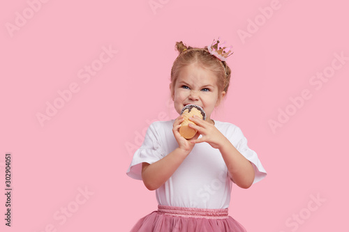 Cute child girl with pleasure eats tasty ice-cream on a pink studio background Wallpaper Mural