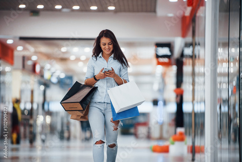 Fototapeta Brunette woman in the supermarket with many of packages and phone in hands have shopping day obraz