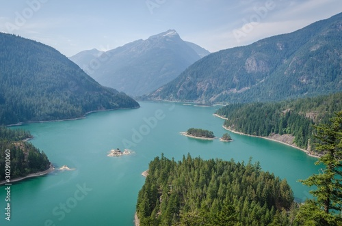 Fotomural High angle shot of the Diablo Lake in the middle of forested mountains under a b